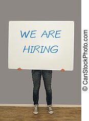 Woman holding we are hiring sign