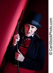 Woman holding whip and wearing top hat