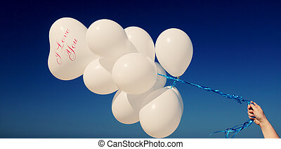 woman holding white balloons on seaside