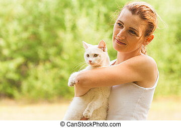 Woman holding white cat in summer park