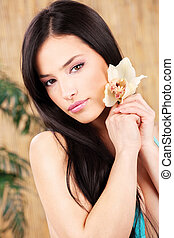 woman holding white orchid