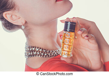 Woman holds a bottle of perfume
