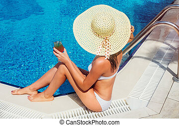 Woman holds a cocktail in the swimming pool