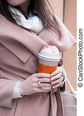 Woman holds a cup of coffee in city center. Street fashion