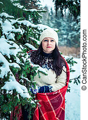Woman holds a cup of coffee in winter forest