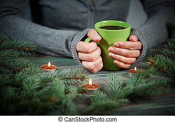 Woman holds a cup of hot tea among the fir branches and candle.