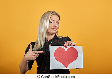 woman holds a sheet of paper with red heart in hands shows direction finger