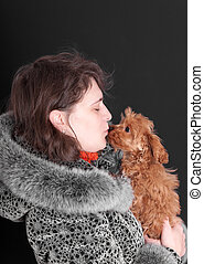 woman holds a small shaggy puppy