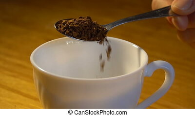 woman holds a spoon and strews coffee to mug. slow motion