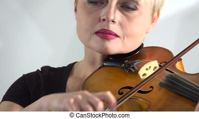 Woman holds a violin playing her bowing over the strings. Close up. White background