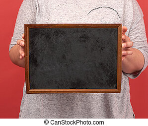 woman holds brown empty wooden frame on red background