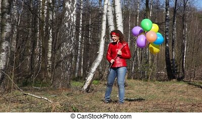 woman holds bunch of balloons and runs - young woman holds...