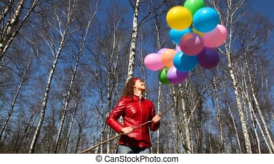 woman holds bunch of balloons in forest - happy smiling...