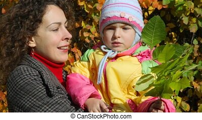 woman holds girl with leaves on hands
