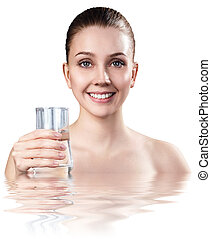 Woman holds glass in water with crystal clear surface.