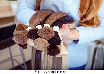 Woman holds hair extension equipment of natural hair. hair...