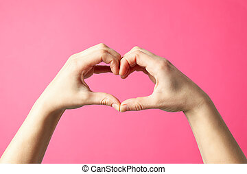 Woman holds hands in the shape of a heart on pink background