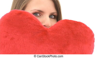 Woman holds heart pillow in front of her face