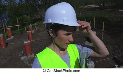 Woman holds helmet and writing near construction site
