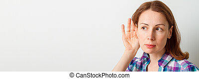 Woman holds her hand near ear and listens