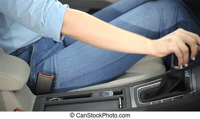 Woman holds her hand on the gear lever