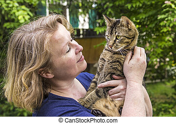 woman holds her tiger cat in the arm