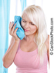 Woman holds ice pack on her cheek - Woman holds an ice pack ...