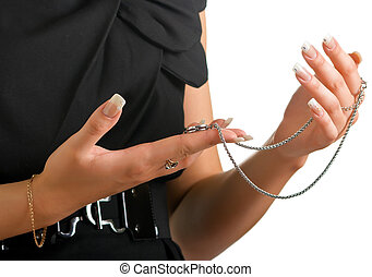 The woman in a black dress holds in hands a jewelery chain with a suspension bracket. Isolation on a white background