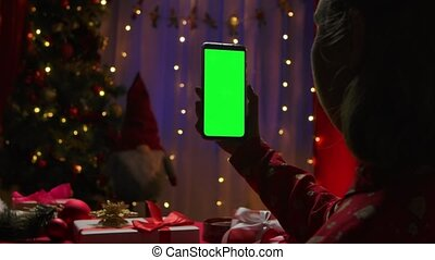 Woman holds in her hand a smartphone with green screen chroma key on the background of a home interior decorated on New Years Eve. Online communication via video chat. Congratulations on social networks. Christmas holidays concept. Close up. Slow motion.