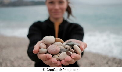 Woman holds in her hands a pile of rocks at the shore with the waves.