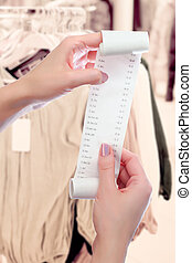 woman holds in her hands roll of paper with printed receipt