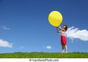 Woman holds  large inflatable ball in hands on wind