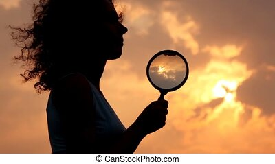 woman holds magnifier and puts it to chin against sky and...