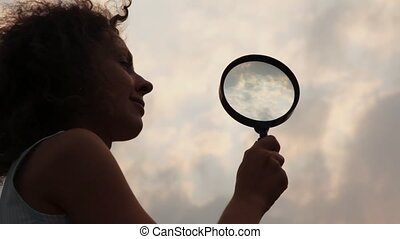 woman holds magnifier and slowly moves to it close up