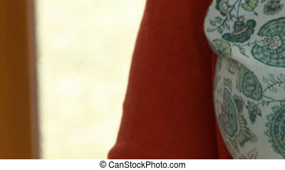 Handheld, close up shot of a woman holding up a maroochi nut in her hand.