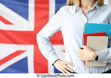 Woman holds notebooks and diaries against background of flags of Britain