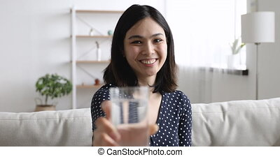 Woman holds out hand with glass of water to camera - Happy ...