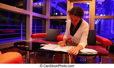 Woman holds pen and reads documents when sits at table in hall of hotel