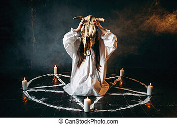 Woman holds skull of the animal in hand, occultism