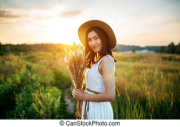 Woman holds wheat bouquet in the field at sunset