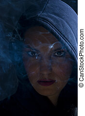 Woman hooded in darkness with smoke