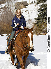 Woman horseback riding in snow. - Young Caucasian woman...