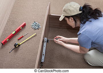 Woman housewife putting together assemble bed frame, using hand tools.