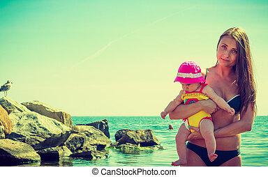 Woman hugging baby in water