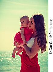 Woman hugging baby on beach near water
