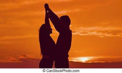 woman hugging man hands behind neck - at sunset girl hugging...