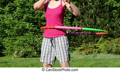 woman hula hoop - closeup of woman chest and waist turn spin...