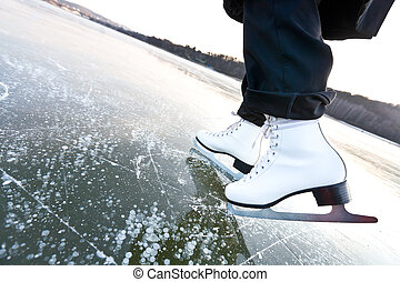 Woman ice skates with overview of a lake