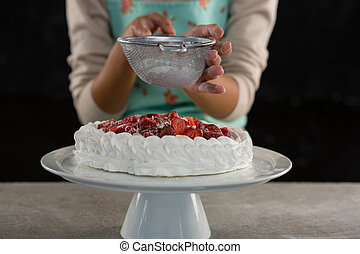 Woman icing sugar on tart - Mid-section of woman icing sugar...