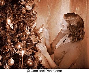 Woman ignites candles on Christmas tree.